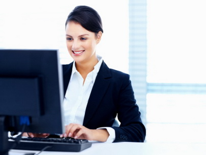 Cute smiling young office worker using a computer with copy space at office